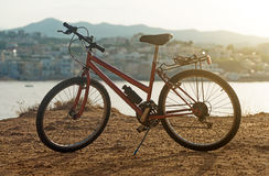 Red bicycle. Red bicycle on the hill at sunset stock photo