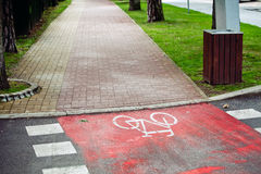 Red bicycle lane with white mark. Stock Photos