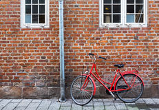 Red bicycle near red wall. Copenhagen, Denmark. Red bicycle near red wall in Copenhagen, Denmark Royalty Free Stock Images