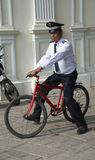 Red bicycle with no brakes being removed by security guard Royalty Free Stock Photos