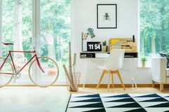 Open workspace with white chair. Red bicycle in open workspace with white chair at desk with laptop and designer lamp Stock Image