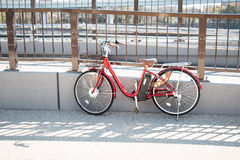 Red Bicycle park at the railing of the bridge on the road Stock Photos