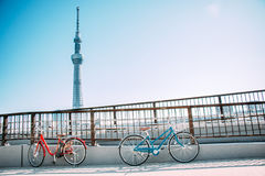 Red Bicycle park at the railing of the bridge on the road. Blue and Red Bicycle park at the railing of the bridge on the road along sumida river, see Tokyo sky Royalty Free Stock Image