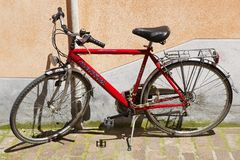 Red bicycle parked in front of the pink wall in Rimini, Italy. Stock Image