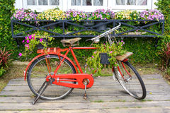 Red bicycle standing in garden Stock Photos