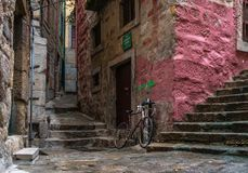 Red bicycle in the street of an old stone little town. With stairs royalty free stock photos