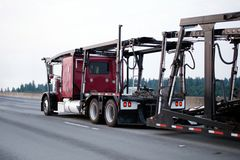 Red big rig classic semi truck car hauler with empty trailer run. A large red powerful big rig car hauler semi truck with an empty two-tiered trailer for Royalty Free Stock Photo