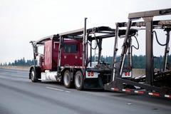 Red big rig classic semi truck car hauler with empty trailer run Royalty Free Stock Photo