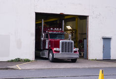 Red big rig classic semi truck unload cargo at warehouse gate Royalty Free Stock Photos