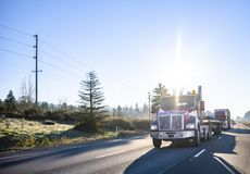 Red big rig day cab semi truck transporting commercial cargo on flat bed semi trailer running in front of semi trucks convoy on. Red big rig industrial grade royalty free stock image