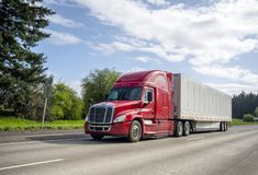 Red big rig popular bonnet semi truck transporting commercial cargo in dry van semi trailer moving on the straight wide highway. Red big rig popular professional stock image