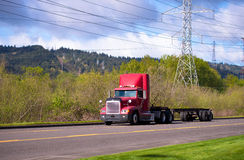 Red Big Rig on the road with power line. Red semi truck with a trailer on the road with power line on a background of green bushes and trees and cloudy sky stock photos