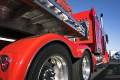 Red big rig semi truck with alumnum flat bed semi trailer standi royalty free stock image