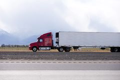 Red big rig semi truck carry refrigeration semi trailer and goin. Side view of bright red big rig semi truck fleet transporting cargo in long refer semi trailer Royalty Free Stock Image