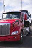 Red big rig semi truck with day cab transporting two another sem Royalty Free Stock Photo