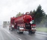 Red big rig semi Truck with tank semi trailer for transportation of chemicals and toxic liquids running on the raining road. Red big rig industrial fright semi stock photography