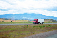 Red big rig semi-truck with trailer going on straight divided hi Stock Photography
