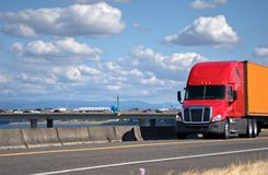 Red big rig semi truck transporting container on the road with r stock image