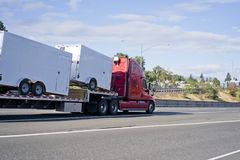 Red big rig semi truck transporting trailers on step down semi t royalty free stock images