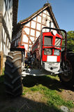 Big red tractor near the house Stock Images