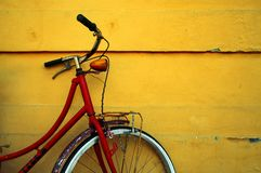 Red Bike. A vintage red bike leaning against an old yellow wall royalty free stock photos