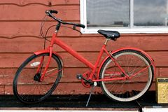 Red bike. Parked against cedar sided building Royalty Free Stock Images