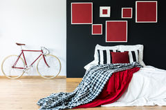 Red bike against white wall. In bedroom with red paintings on black wall above king-size bed Stock Photography