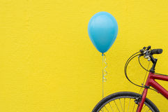 Red bike, blue balloon, bright yellow wall Stock Image