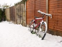 red bike cover in snow rested again fence snow covering ground w royalty free stock images