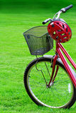 Red bike and a helmet on green grass Royalty Free Stock Image
