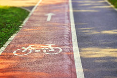 Red bike lane. On sidewalk with painted white bicycle and arrow signs. Copy space Stock Image