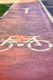 Red bike lane. On sidewalk with painted white bicycle and arrow signs. Copy space Royalty Free Stock Photos
