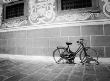 Red bike leaning against a wall in black and white Stock Photography
