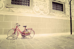 Red bike leaning against a wall in vintage tone Royalty Free Stock Image