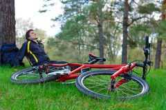 Red Bike Lying on Green Grass. Cyclist Relaxes Royalty Free Stock Photography