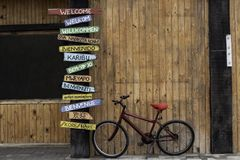 Red Bike Next to a Welcome Sign. Red Bike Next to a Post with Welcome Signs in Several Different Languages found in Namibia. English, Afrikaans, German, Xhosa stock photos