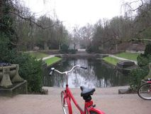 A red bike parked in front of a lake in the Muziekkoepel Noorderplantsoen Park in Groningen, The Netherlands stock photo