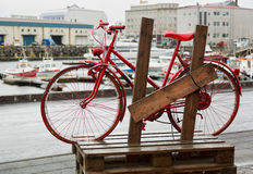 Red bike on rustic bicycle rack. Royalty Free Stock Photo