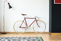 Red bike in living room. Red bike in simple living room with design lamp and patterned black and white carpet Stock Photo