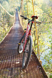 Red bike standing in suspension bridge Stock Photos