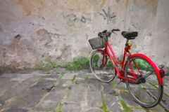 Red bike standing by textured old wall, oil style. Royalty Free Stock Image