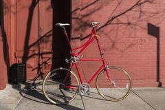 Red bike in the street with brick wall background Royalty Free Stock Photography