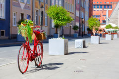 Red bike on the street. An old stylized red bike with baskets full of flowers standing on the street Royalty Free Stock Photo