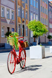 Red bike on the street. An old stylized red bike with baskets full of flowers standing on the street Stock Photos