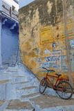 Red bike, yellow wall and blue stairs Stock Photography