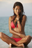 Red Bikini Beach Model. Beautiful young Asian model wearing bright red bikini laying on Thailand beach on sunny day stock images