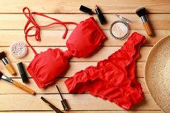 Red bikini and cosmetics. On wooden background stock photos