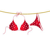 Red bikini suit with white dots hanging on rope Royalty Free Stock Image
