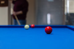 Red billiard ball with a man playing background Stock Image