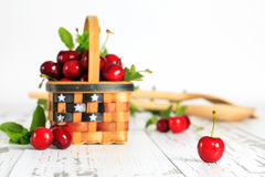 Red Bing Cherries Basket. A single ripe Bing cherry on white wood surface with patriotic themed basket filled with cherries blurred in background Stock Photos